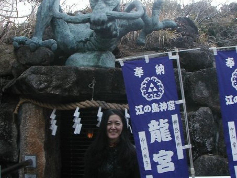 Eiko Hosaka Tiernan, vocalist of nature airliner, at an antique shrine near the island's apex.
