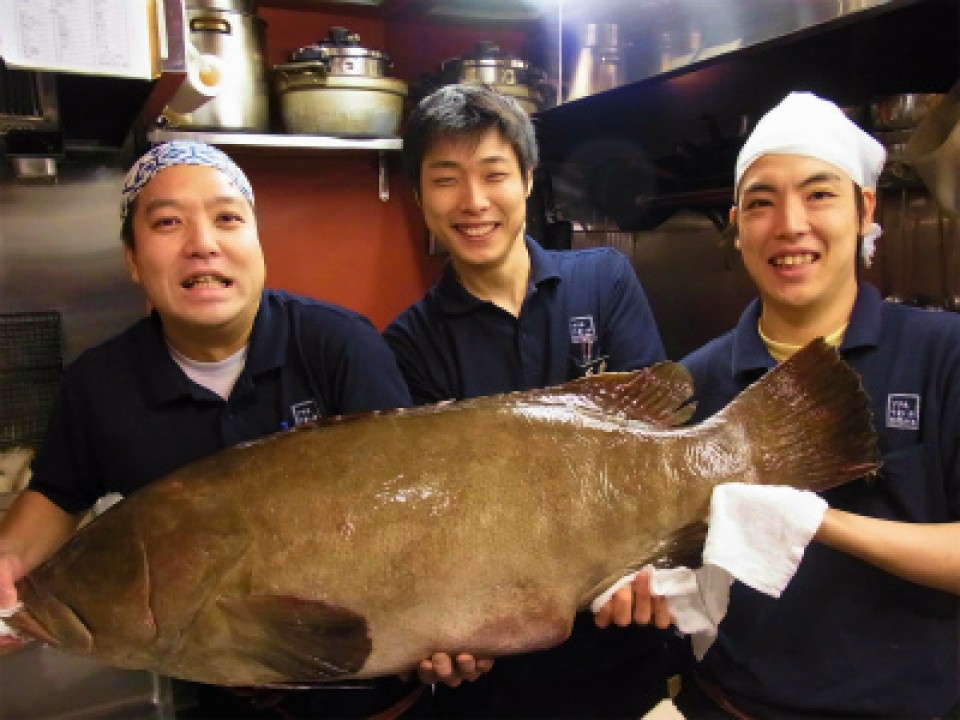 Young, Friendly and Vigorous Staff Members Holding Fresh Longtooth Grouper